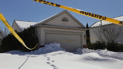 Police tape surrounds the Pontiac, Mich., house March 6, 2014, where a woman in her 40s was found dead in the back seat of her SUV in her garage, where she may have been there as long as six years.