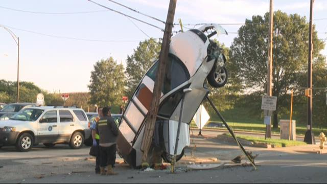 SUV pinned vertically against power pole after uptown wreck
